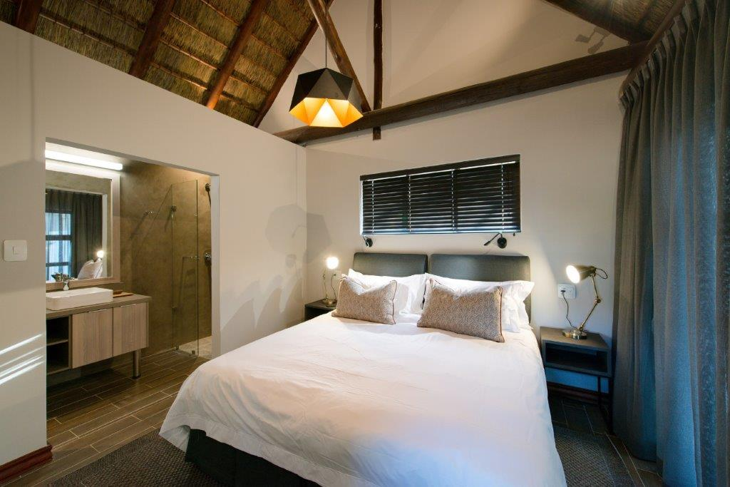 Bucklers Africa Lodge bedroom with thatched roof and ensuite bathroom