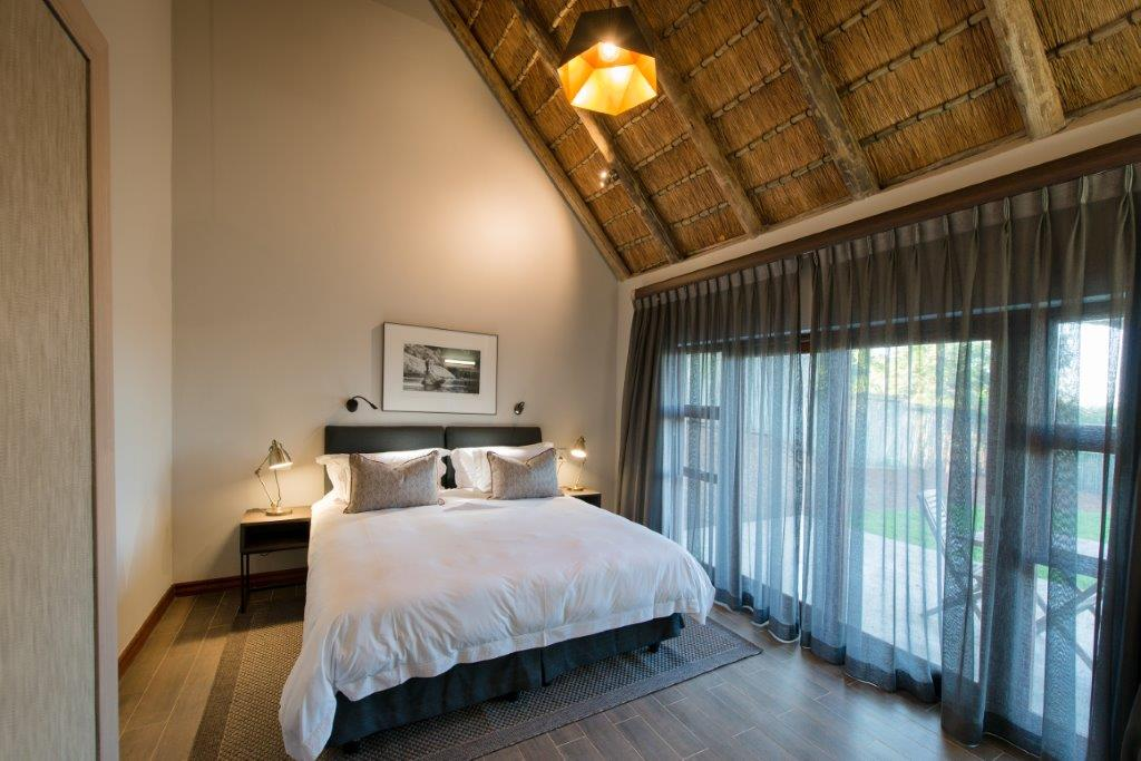 Bucklers Africa Lodge bedroom with white linen, thatched roof and subtle decor