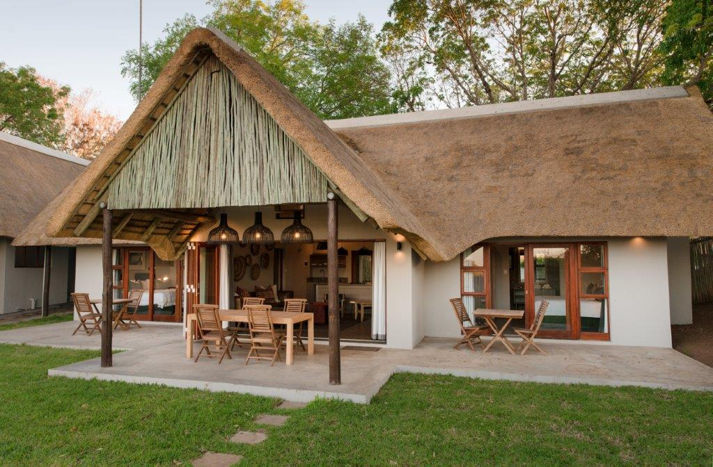 Bucklers Africa Lodge self-catering unit with thatched roof, green grass garden